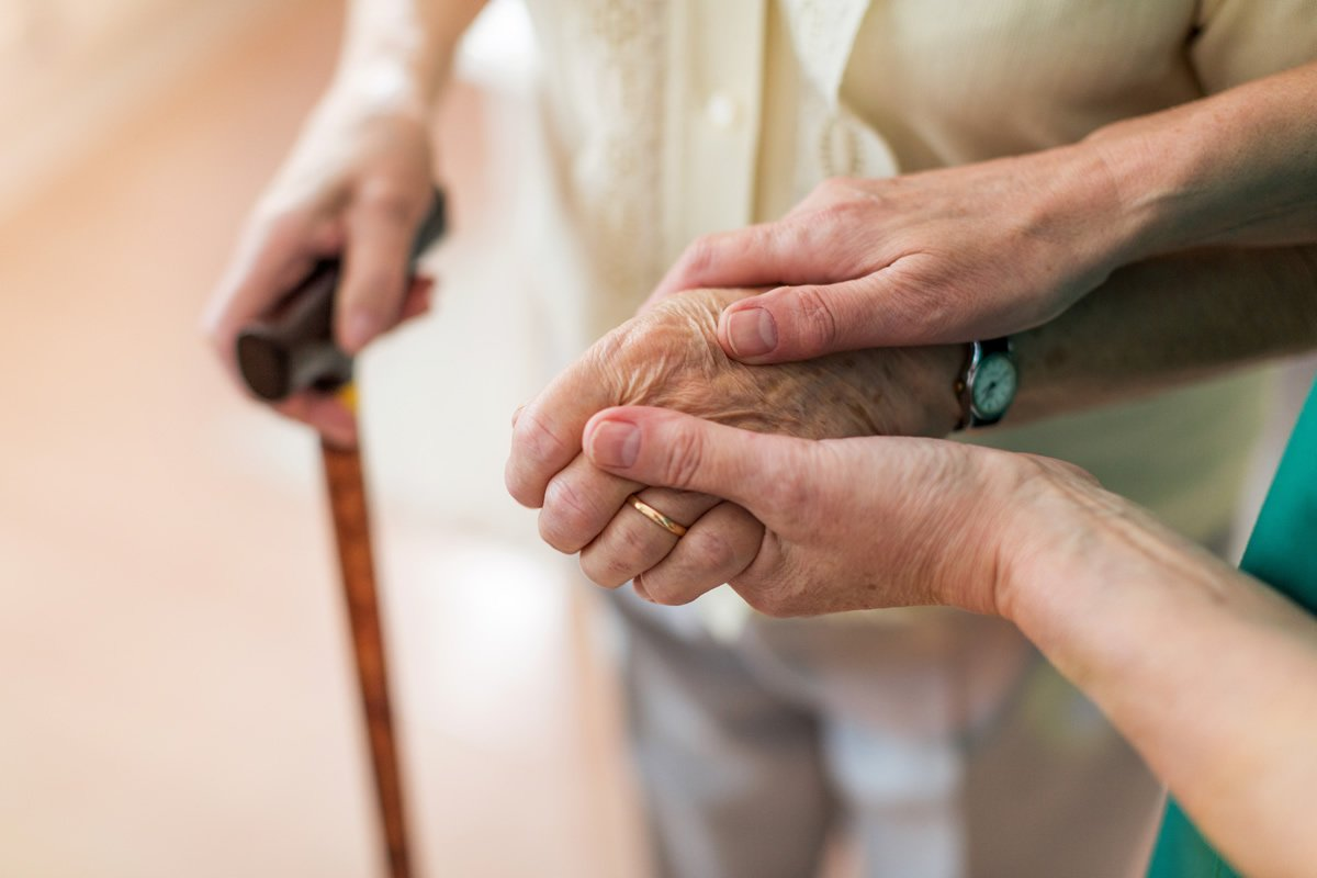 hands guiding elderly woman with a cane